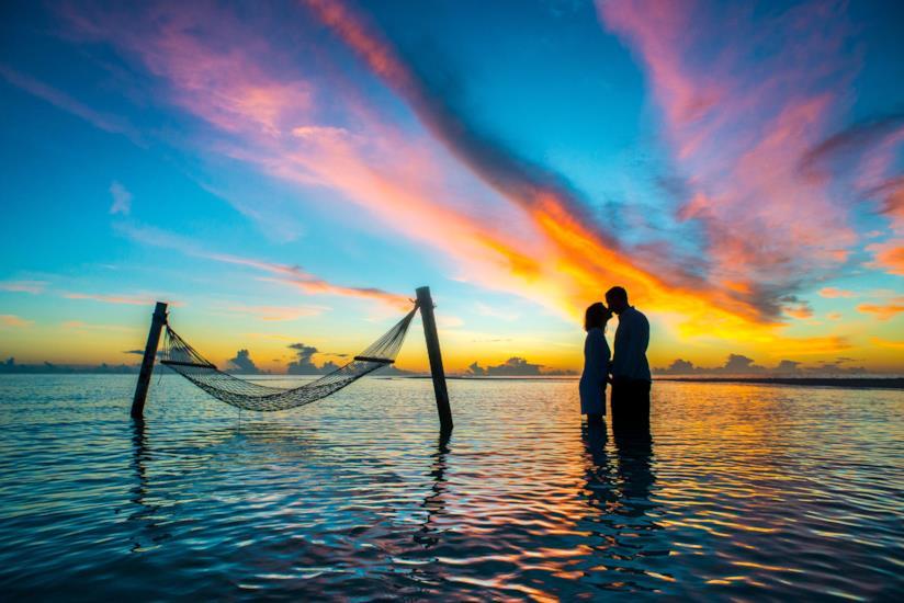 Coppia si scambia un bacio al tramonto nel mare