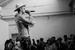 Achille Lauro, in piedi, con una camicia ghepardata, un cappello e il microfono in mano