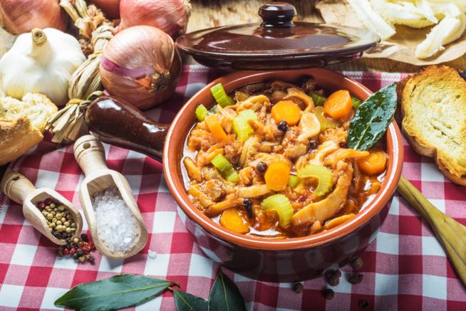 Tegame in terra cotta con all'interno trippa e verdure su tavola a quadri bianca e rossa con ingredi