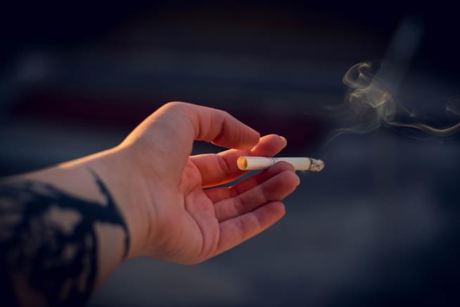La mano di una persona che tiene una sigaretta accesa