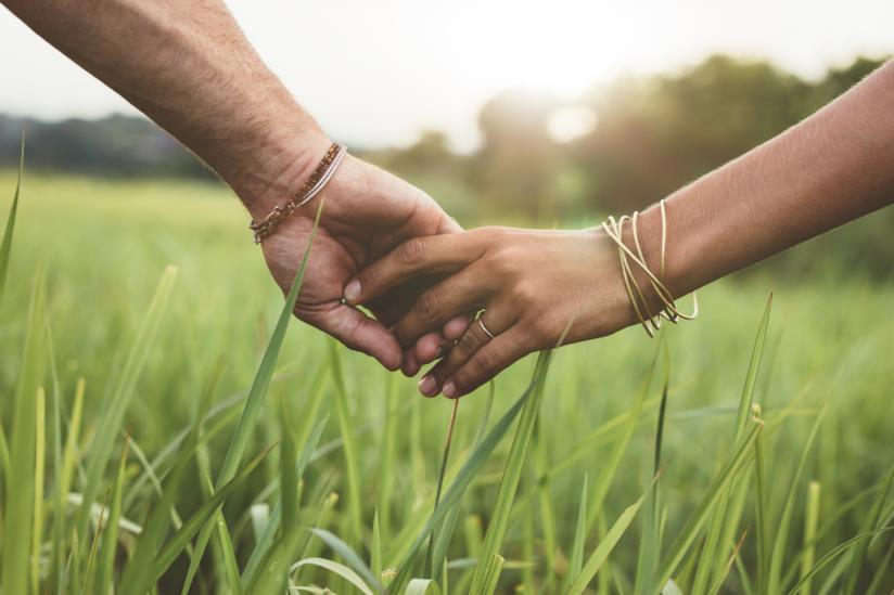 Due mani, una maschile e una femminile, si tengono per mano passeggiando in un prato