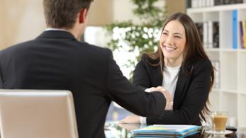 Un uomo e una donna in ufficio si stringono la mano