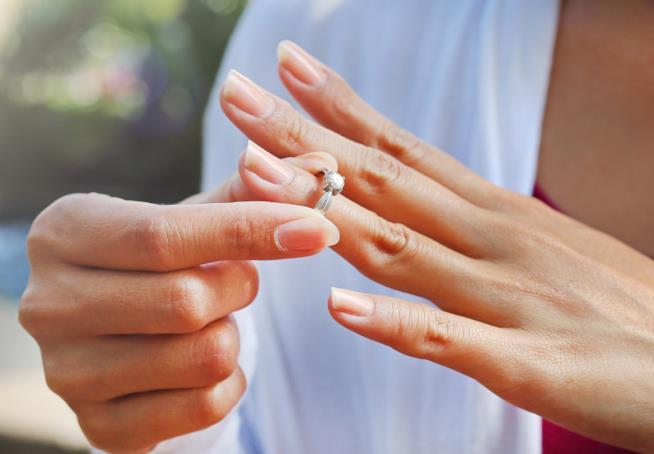 Una ragazza si sfila un anello di fidanzamento dalla mano