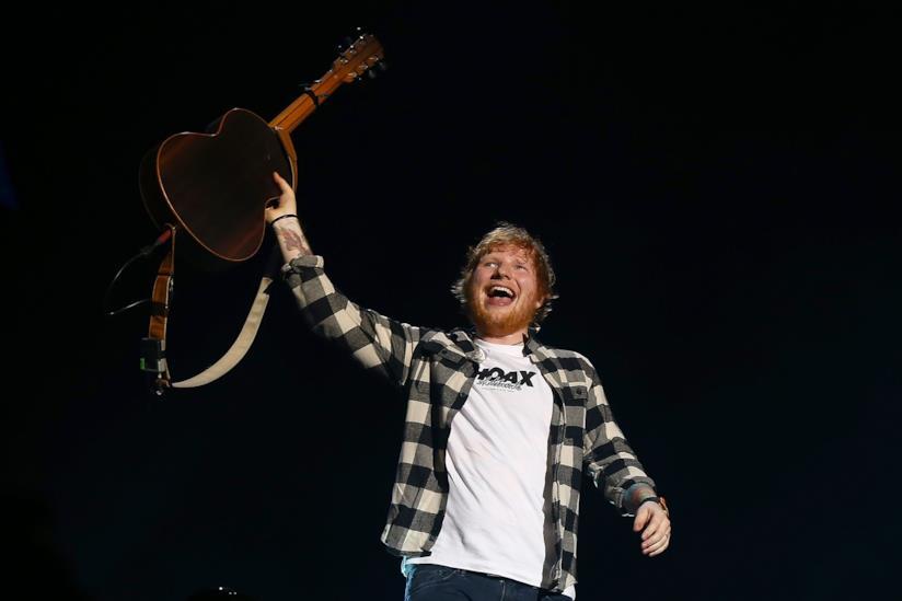 Ed Sheeran, sorridente, in piedi, tiene la chitarra sollevata con la mano sinistra