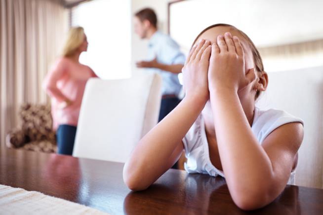 Un bambino di copre il viso mentre i genitori litigano