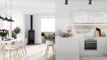 Angolo cottura posizionato lungo una parete in soggiorno, arredato con mobili bianchi moderni