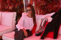 Nina Zilli, con una maglia bianca e dei pantaloni grigi, seduta su un divano, davanti a delle piante