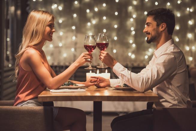 Uomo e donna brindano a cena in un ristorante