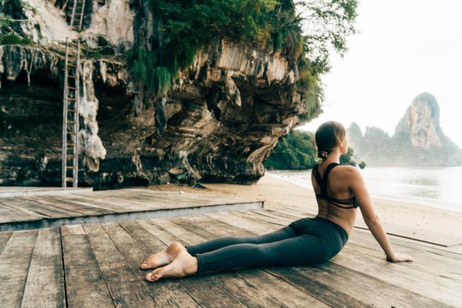 Una ragazza pratica yoga all'aperto su un pontile