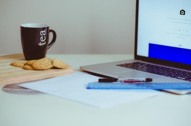 Macbook acceso e tazza di the.