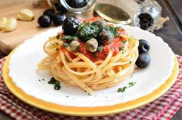 Piatto con linguine, capperi,  olive nere e prezzemolo in un piatto bianco e giallo e su tovaglia