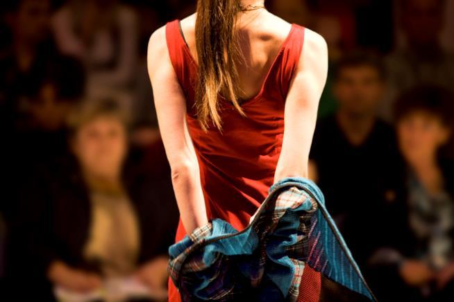 una ragazza con vestito rosso sfila vista da dietro mentre si leva una giaccia