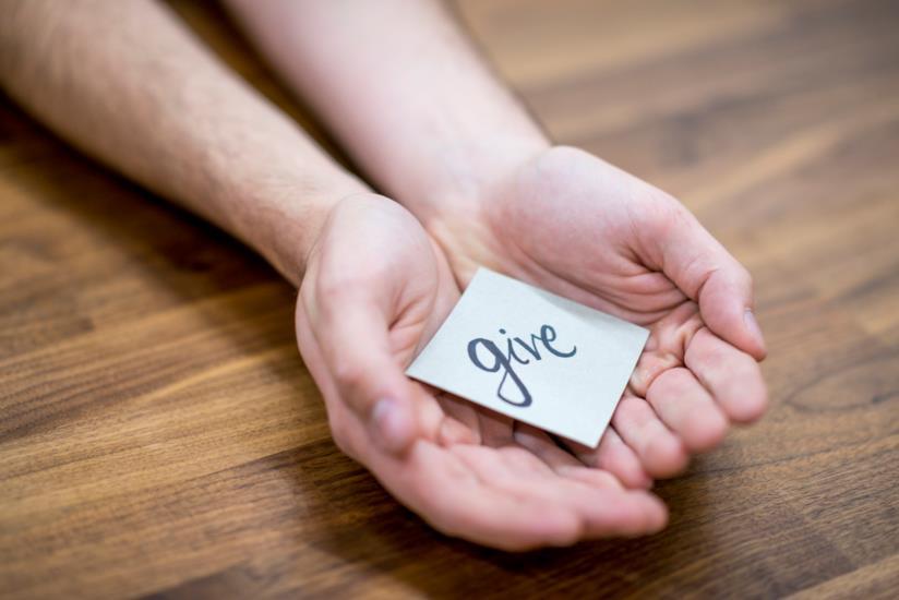 Una mano che tiene un bigliettino con scritto 'Give'.