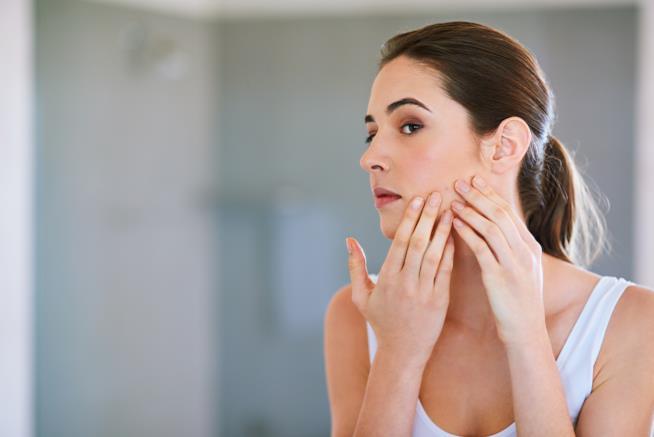 Una donna si guarda il viso colpito da acne