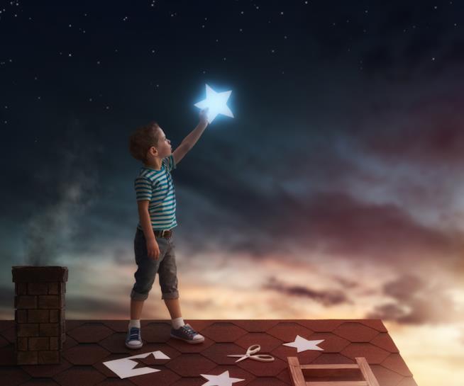Un bambino tiene in mano una stella nella notte di San Lorenzo