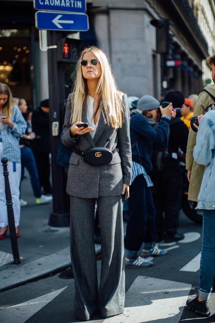 Blazer grigio e pantaloni coordinati indossati con camicia e marsupio
