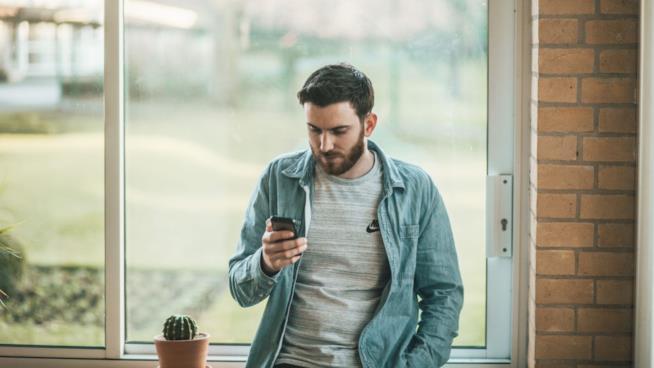 Una ragazzo  guarda il suo smartphone