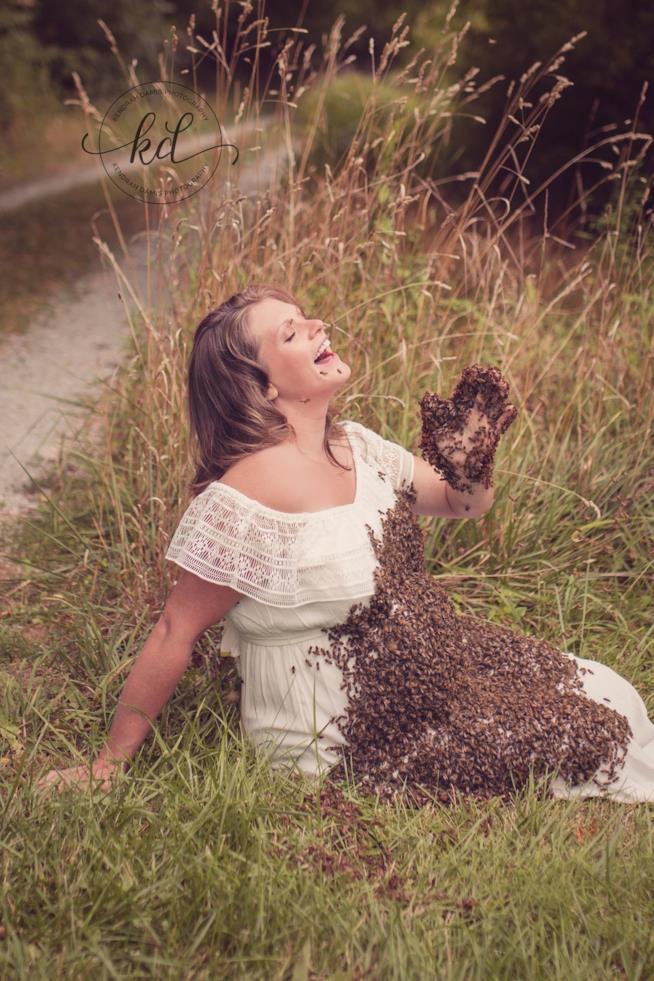 Un'apicoltrice posa col pancione coperto di api