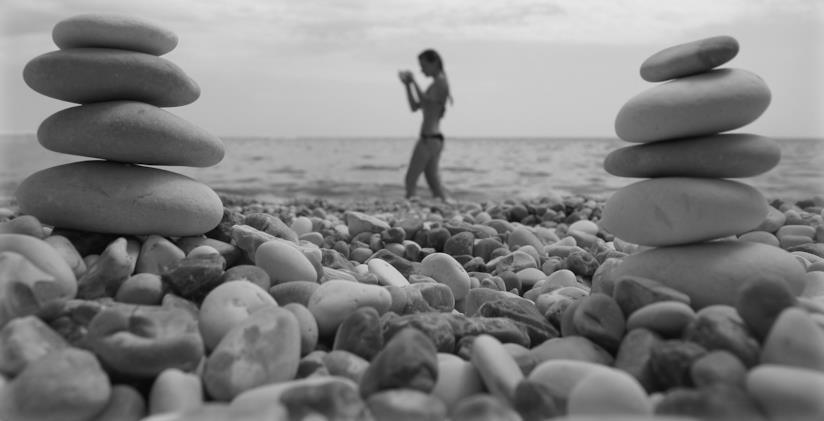 Bianco e nero, spiaggia di sassi in primo piano, sullo sfondo una ragazza in bikini in acqua