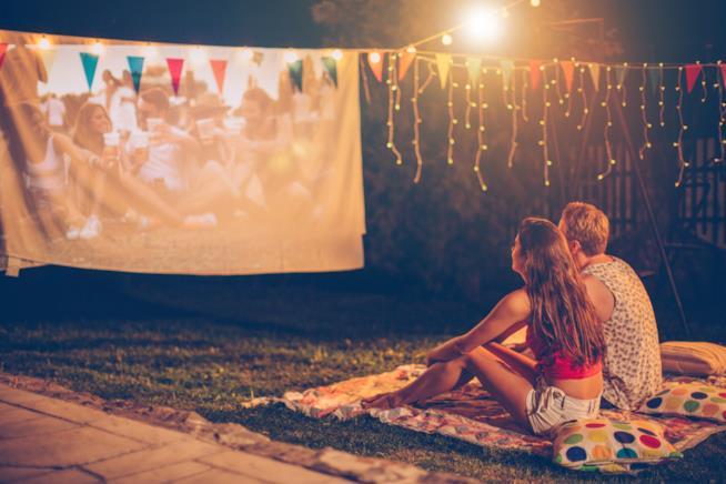 due ragazzi sono seduti all'aperto su una coperta in un prato davanti ad un film proiettato