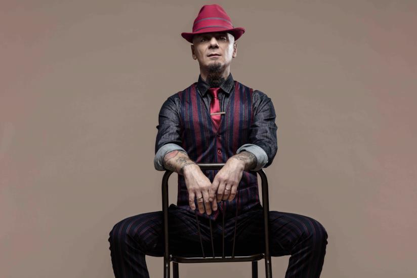 J-Ax seduto al contrario su una sedia, con la cravatta e il cappello rossi