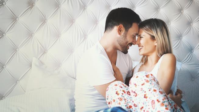 Una ragazzo e una ragazza si abbracciano mentre sono su un letto in una camera bianca