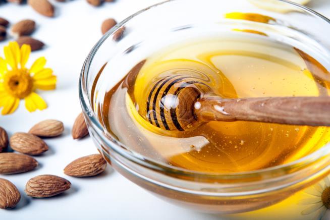 miele con il dosatore, mandorle e un fiore giallo