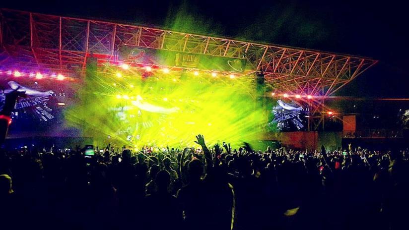Pubblico a un festival con le braccia alzate e luce gialla dal palco