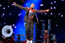 Justin Timberlake in piedi, con le braccia aperte, sul palco, con dietro dei led