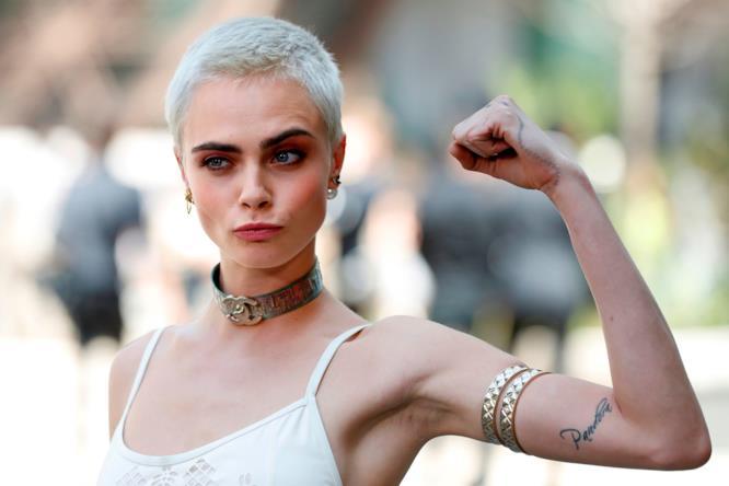 Cara Delevingne con un braccio alzato alla sfilata Chanel