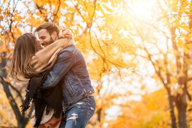 Una coppia si abbraccia in un bosco autunnale