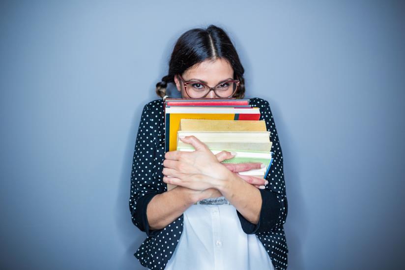 Una ragazza si nasconde dietro a dei libri