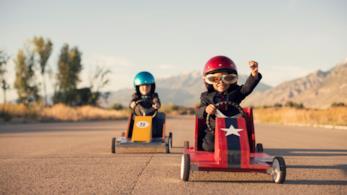 Un bambini su un auto giocattolo taglia per primo il traguardo
