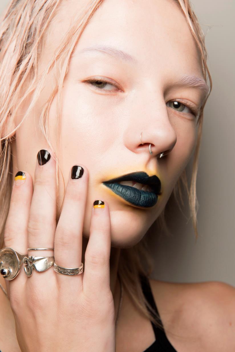 Nail art in gel nero con linee gialle