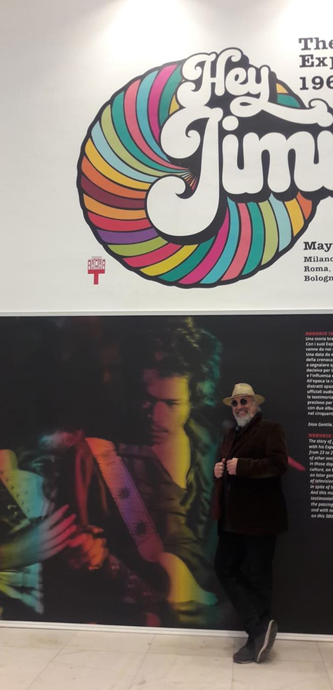 Eugenio Finardi, in piedi, sorridente davanti a una foto di Jimi Hendrix