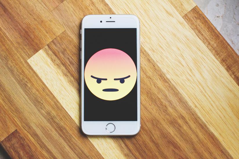 Smartphone con emoji rabbiosa