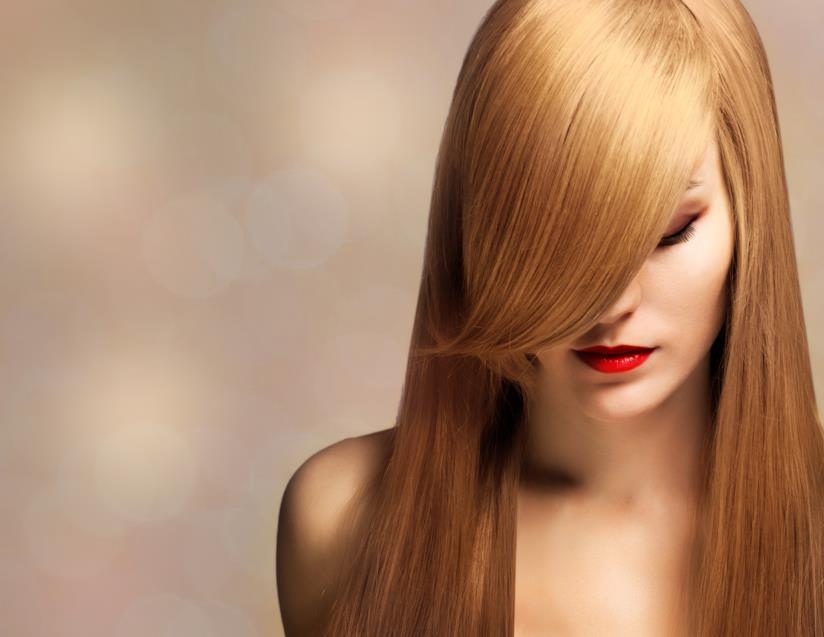 primo piano di una ragazza con capelli lunghi biondi, pelle chiara, truccata con rossetto rosso, occhi chiusi ed abbassati