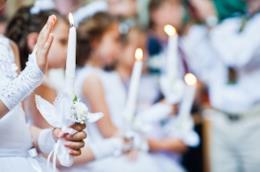Bambina durante il rito della Cresima che tiene in mano una candela