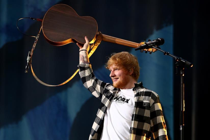 Ed Sheeran, in piedi, con una camicia a quadri, tiene in alto la chitarra stringendola con la mano