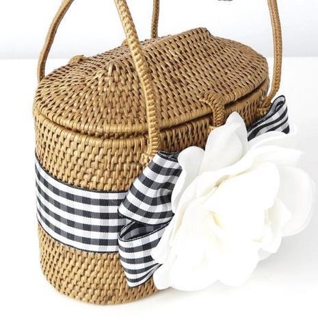 Una borsa di paglia con fiocco e fiore