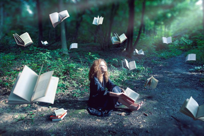 Donna seduta in un bosco circondata dai libri