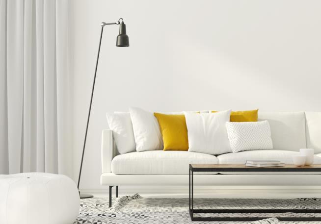 Lampada da terra in metallo verniciato nero posta accanto al divano in soggiorno