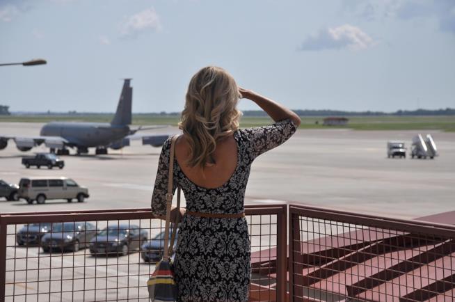 Una donna di spalle che guarda gli aerei partire.