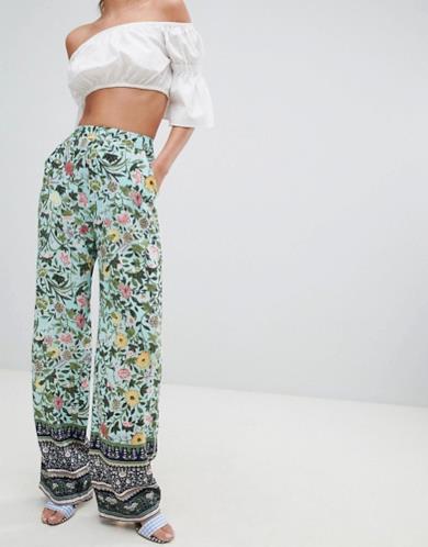 Pantaloni palazzo con stampa a fiori e bordo decorato