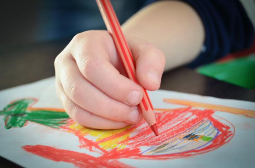 Un bambino disegna con matite colorate