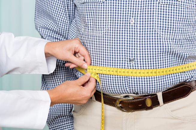 Un medico misura il girovita di una persona