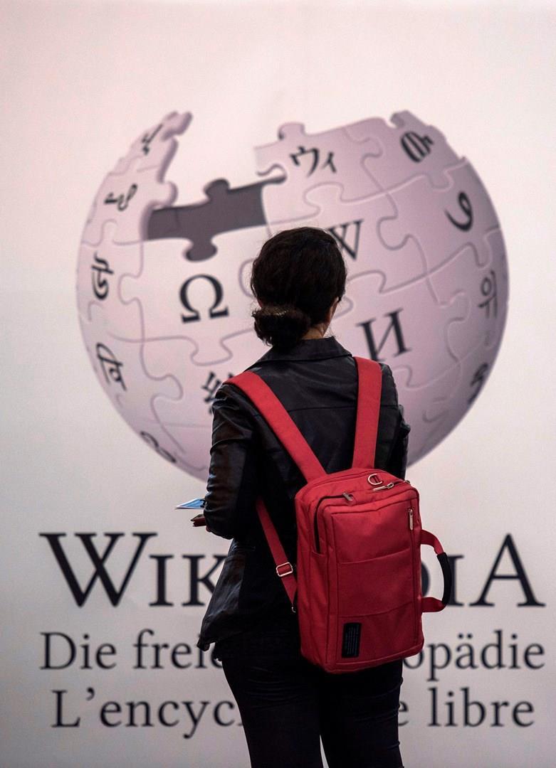 Una persona davanti al logo di Wikipedia.