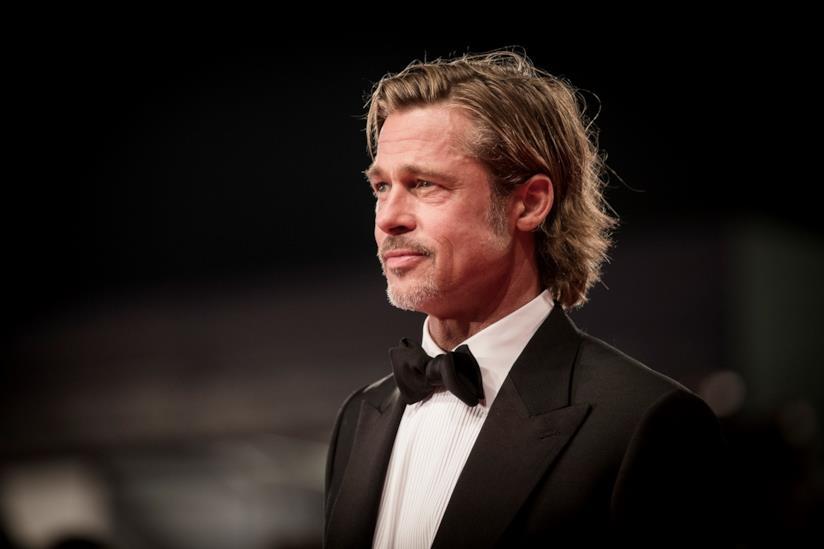 Brad Pitt, di profilo, con un abito nero e una camicia bianca, su sfondo nero