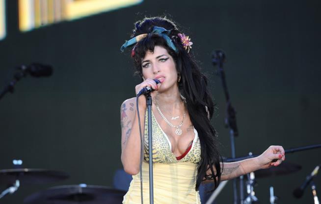 Amy Winehouse canta al microfono, indossando un abito giallo