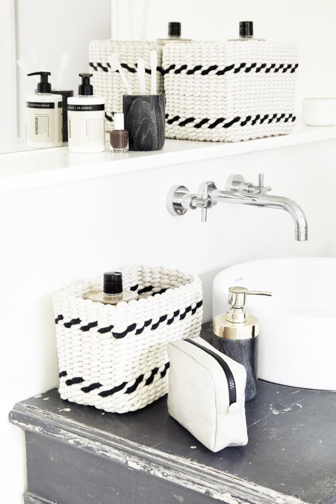Hubsch, cestini bianchi decorati a righe nere disposti sul ripiano del lavabo per contenere gli accessori da toilette